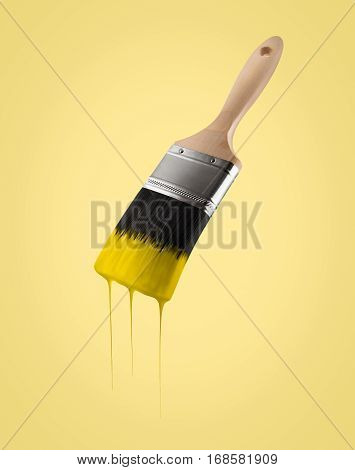 Paintbrush loaded with yellow color dripping off the bristles on yellow background.