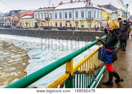 Uzhgorod Ukraine - February 3 2017: A girl from the bridge takes pictures on a mobile phone ice drift on the river.