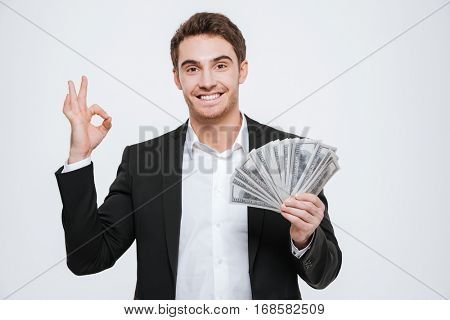 Photo of young cheerful businessman standing at studio holding money in hands make okay gesture. Isolated over white background. Look at camera.