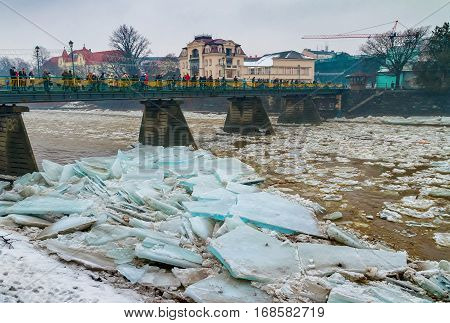 Uzhgorod Ukraine - February 3 2017: Pedestrians watch from the bridge on the ice drift on the river.