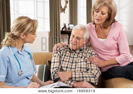 Senior Couple Talking To Health Visitor At Home