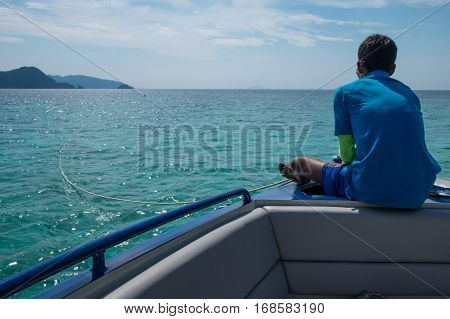 A seaman sitting lonely on boat looking at horizon