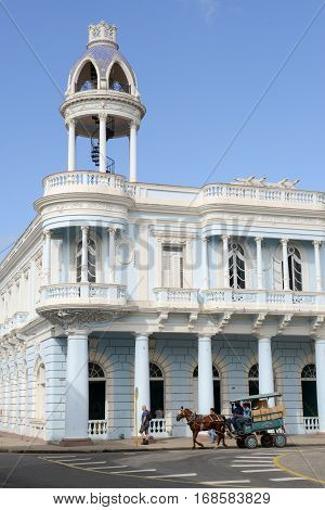 Cienfuegos Cuba - 18 january 2016: People riding a carriage drawn by a horse in front of colonial architecture at the old town of Cienfuegos Cuba