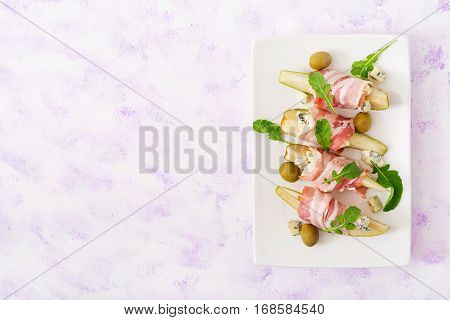 Appetizer With Pear, Blue Cheese, Prosciutto Ham And Toast For Holidays On A White Plate. Flat Lay.