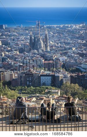 People enjoying the view of the city of Barcelona from the Bunker of Carmel viewpoint. The Mediterranean sea, Sagrada Familia Basilica
