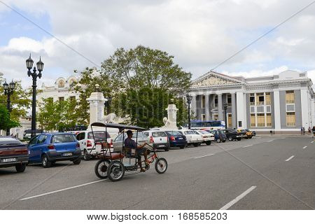 Cienfuegos Cuba - 18 january 2016: People riding a bike in front of San Lorenzo school building on Jose Marti square park in Cienfuegos Cuba