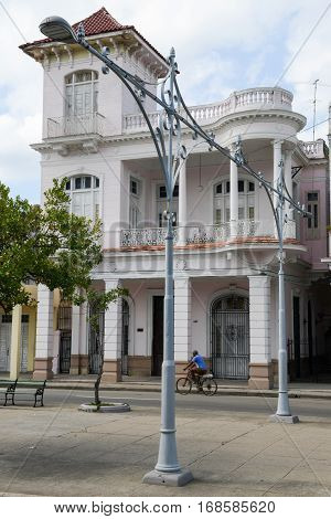 Cienfuegos Cuba - 18 january 2016: Man riding a bike in front of colonial architecture at the old town of Cienfuegos Cuba