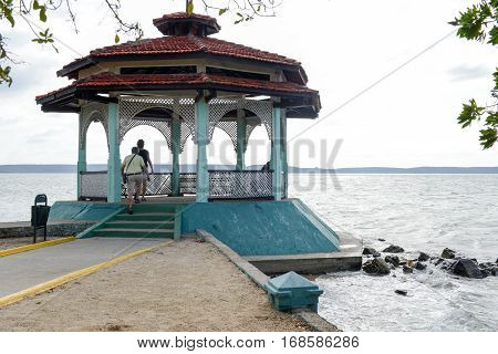 Cienfuegos Cuba - 18 january 2016: people walking in front of the pavilion at the park of La Punta in Cienfuegos with a view on the lagoon Cuba