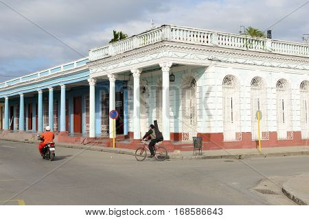 Cienfuegos Cuba - 18 january 2016: People riding a bikes in front of colonial architecture at the old town of Cienfuegos Cuba