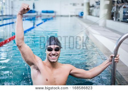 Handsome man triumphing with raised arms in the pool
