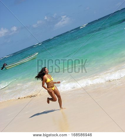 Latin woman running on caribbean beach.