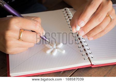 Hand on white pill medicine stock photo