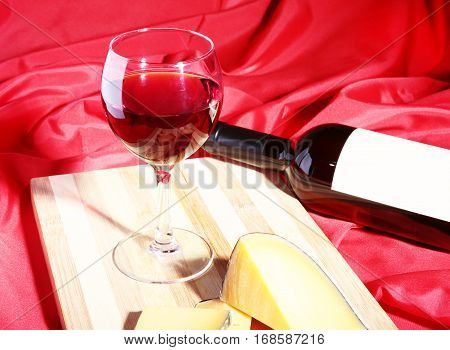 Still life with red wine grapes and chees on wooden table