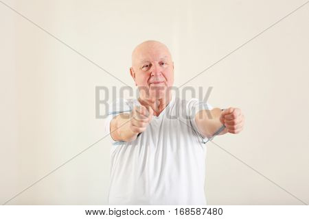 Senior man training with stretching band in rehabilitation center