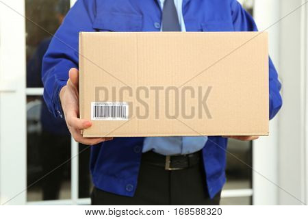 Courier with parcel on doorstep, closeup poster