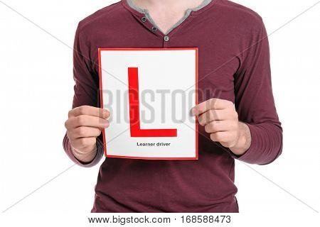 Young man with learner driver sign on white background, closeup
