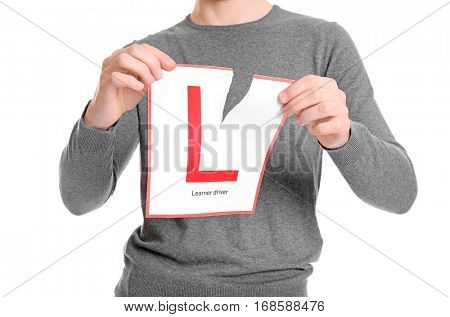 Young man tearing learner driver sign on white background, closeup