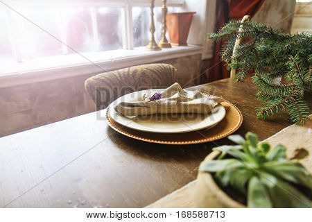 plates of gold on the old oak table in the interior with sunny hotspot, retro style, vintage, aristocratic manners