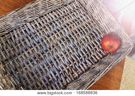 lonely apple lying on the bottom woven box, last residue fruit basket, vintage