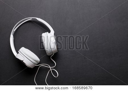Headphones on leather desk table. Top view with copy space. Music concept