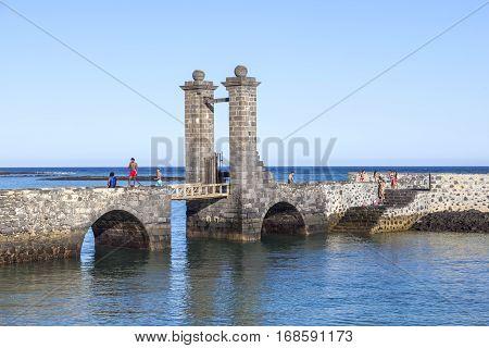 Young People Enjoy Swimming At Castle Castillo De San Gabriel In Arrecife