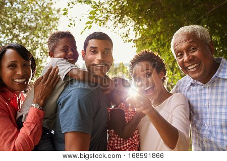 Multi generation black family in garden look to camera
