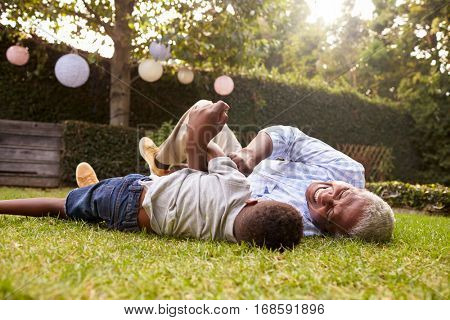 Grandfather and grandson play lying on grass, low angle