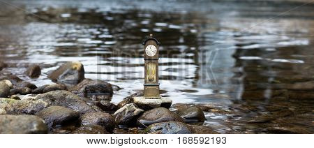 Model standing clock stands on a pebble by the waterside