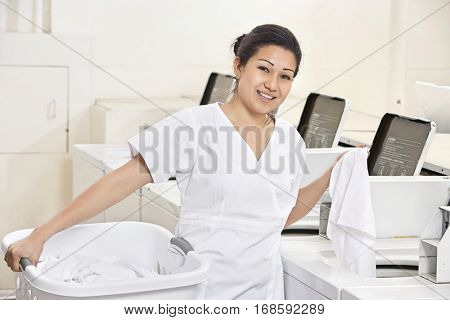 Portrait of a happy young employee standing by washing machines in Laundromat