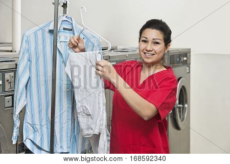 Portrait of a happy young woman with shirt hanging in Laundromat