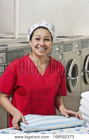 Portrait of a cheerful young woman with towel in Laundromat