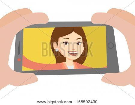 Young joyful caucasian woman making selfie. Smiling woman making selfie with cellphone. Woman taking selfie. Vector flat design illustration isolated on white background.