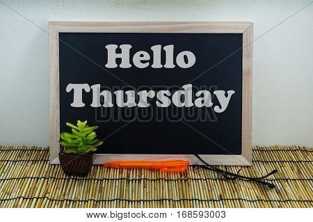 Business & creative concept,Hello Thursday word on blackboard with green plant,pen & spectacle eyeglasses.