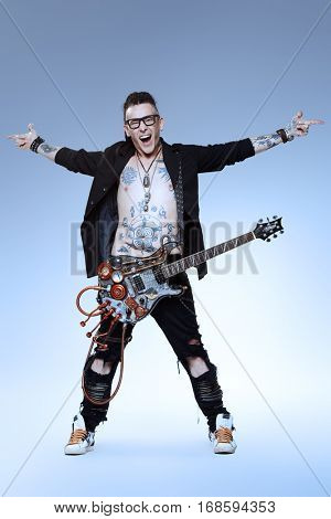 Excited rock musician is playing electrical guitar. Full length studio shot. Entertainment and musical concept.