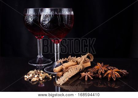 Two wineglasses of wine and different kinds of flavoring