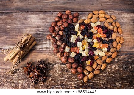Different kinds of nuts and dried fruits in the shape of heart and flavoring