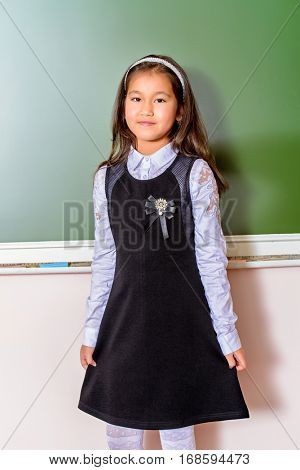 Portrait of a schoolgirl in uniform standing by a schoolboard in a classroom. Educational concept.