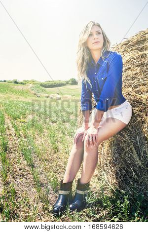 Cowgirl near bale of hay. Young blonde woman outdoors in a meadow.