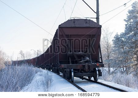 Snowy railway runs in the winter forest, freight train