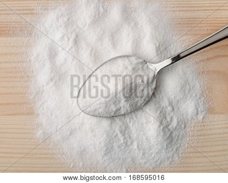 Top view of spoon with baking soda on wooden background