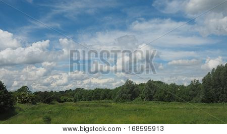 English countryside seen from a train to London with selective focus on the horizon and motion blur on the foreground