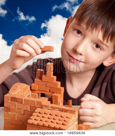 Boy building house isolated on white