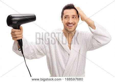 Happy man in a bathrobe drying his hair with a hairdryer isolated on white background