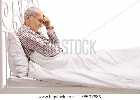 Worried senior lying in bed isolated on white background
