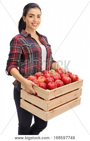Happy female farmer holding a wooden crate filled with apples isolated on white background