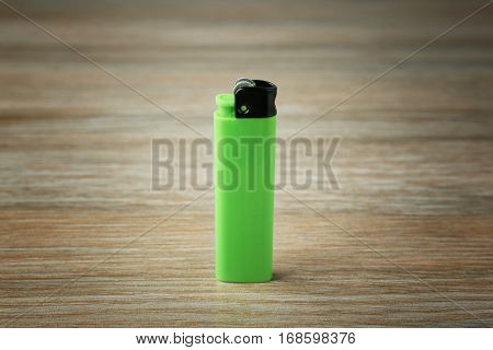 Blank green cigar lighter on wooden background