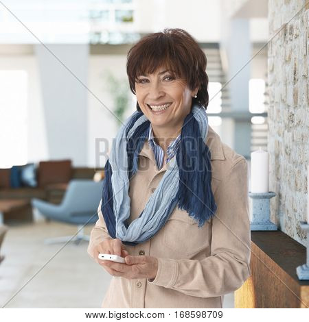 Happy mature woman standing in living room, using mobilephone, smiling, looking at camera.