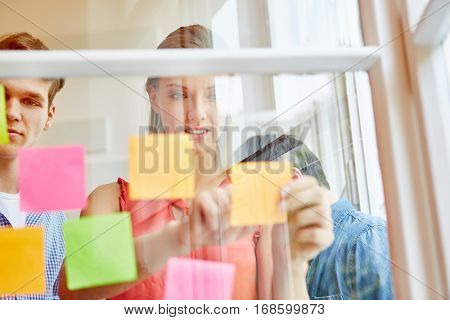 Business people taking notes in sticky notes in a start-up workshop