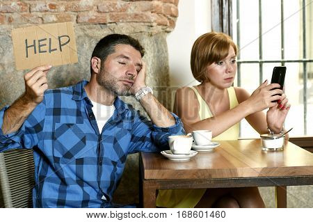 young American couple at coffee shop with internet and mobile phone addict woman ignoring bored sad and frustrated man boyfriend or husband in relationship problem asking for help