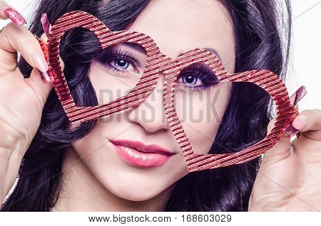 St. Valentine's Day. Woman on a white background close-up with glasses in the shape of heart